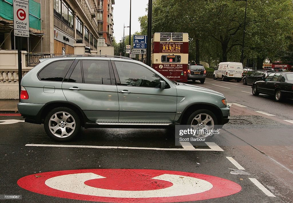 A 4x4 vehicle drives past a congestion charge sign painted on the road on October 25, 2006 in London, England. Gas-guzzling vehicles are being targeted by local authorities to face higher costs for being on the road in Britain. The cost of residents' parking permits could be linked to car emissions for Richmond upon Thames residents, while London's existing congestion charge could rise to GBP 25 per day in 2010 for drivers of high-emissions vehicle.