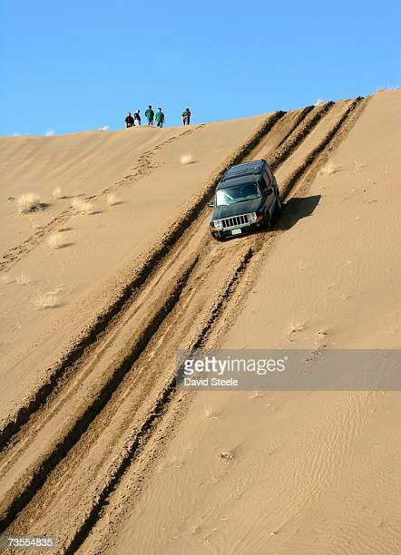 4x4 Vehicle Driving Down a Large Dune with Silhouetted People at the Top