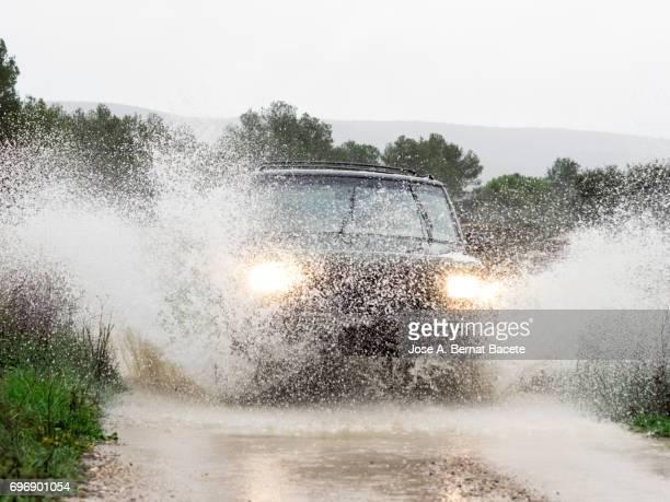 4x4 vehicle on muddy road splashing past a large puddle of rainwater, Spain.