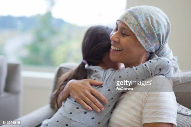 50ish Hawaiian woman wearing headwrap hugging granddaughter