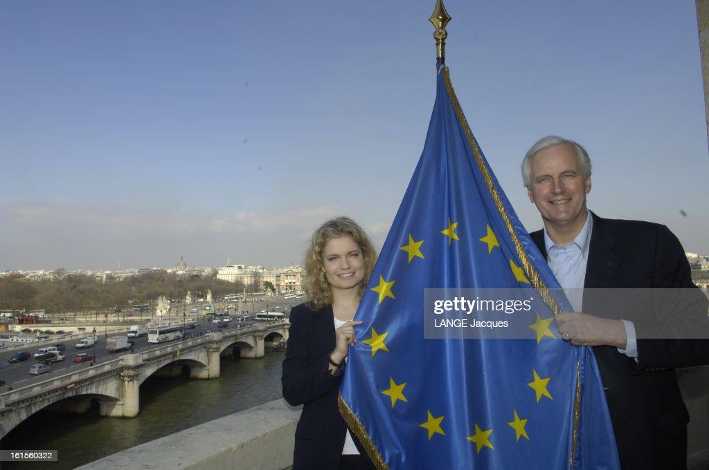50th Anniversary Of The Treaty Of Rome. Plan de face souriant de Sarah BIASINI et Michel BARNIER posant sur une terrasse avec le drapeau européen à l'occasion de la fondation de l'Union européenne, dont on fêtera le cinquantenaire le 25 mars 1956.