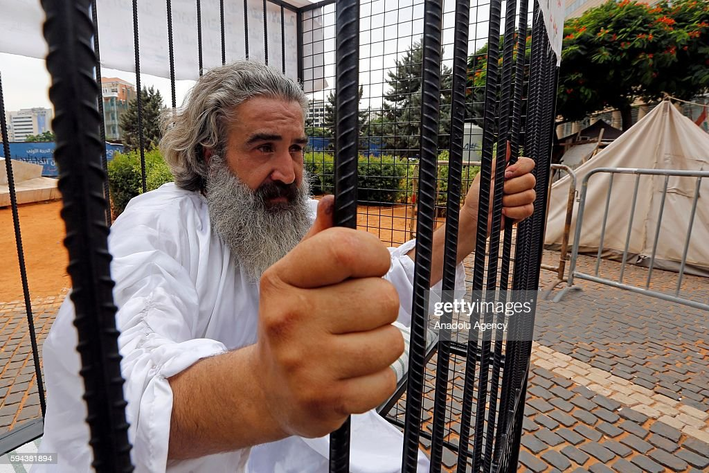 A 50yearsold man 'Mliad' stages a protest inside a cage symbolize a prison at Riad Al Solh Square in Beirut Lebanon on August 23 2016 A poster...
