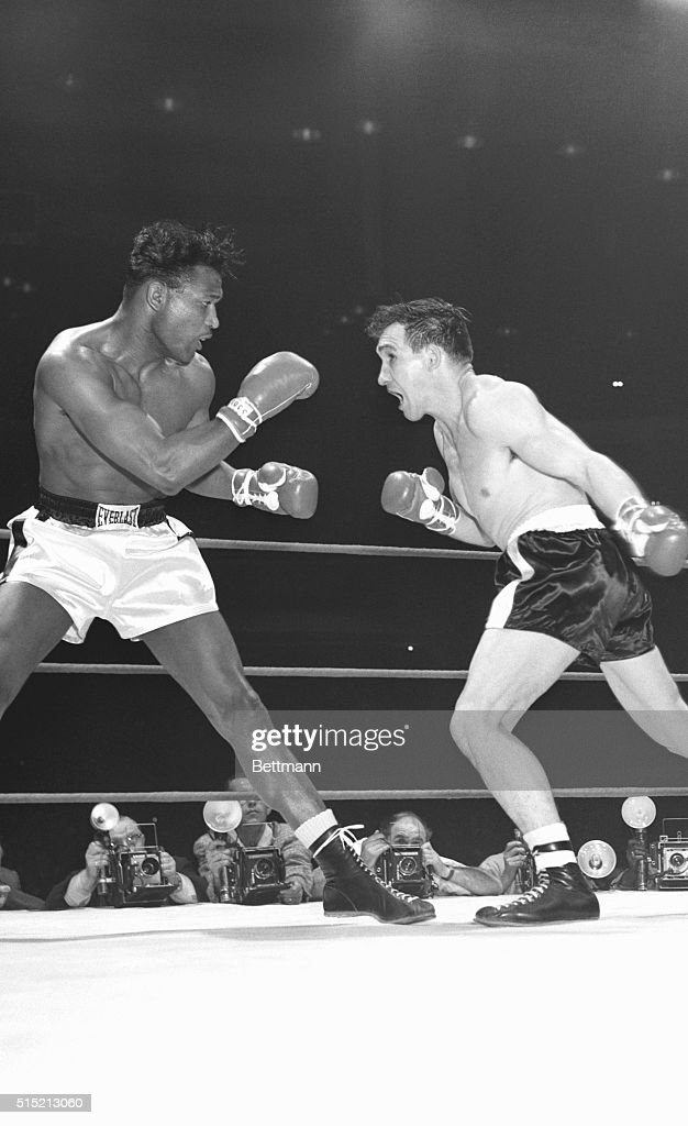 As Sugar Ray Robinson backs away middleweight champion Gene Fullmer charges across the ring to throw a sweeping left in the first round of their...