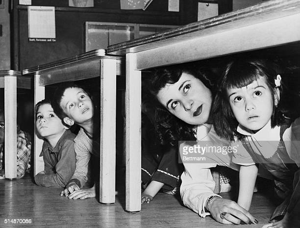 School children and their teacher peer from beneath the table where they took refuge at Lafayette Street School when the sirens howled the alert in...