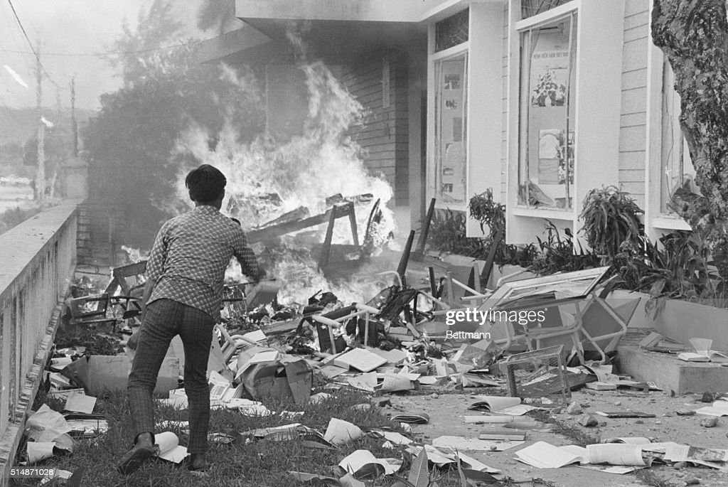 An anti-government student throws books and papers in to the flames at the United States Information Service Library building here. Buddhist youths ransacked the library and burned its books, furnishings, and building.