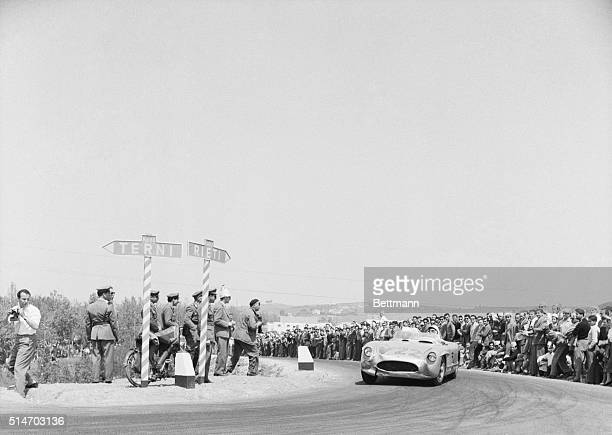 His lowslung Mercedes racing car clinging to the road British driving ace Stirling Moss races his car around a curve near Rome on his way to win the...