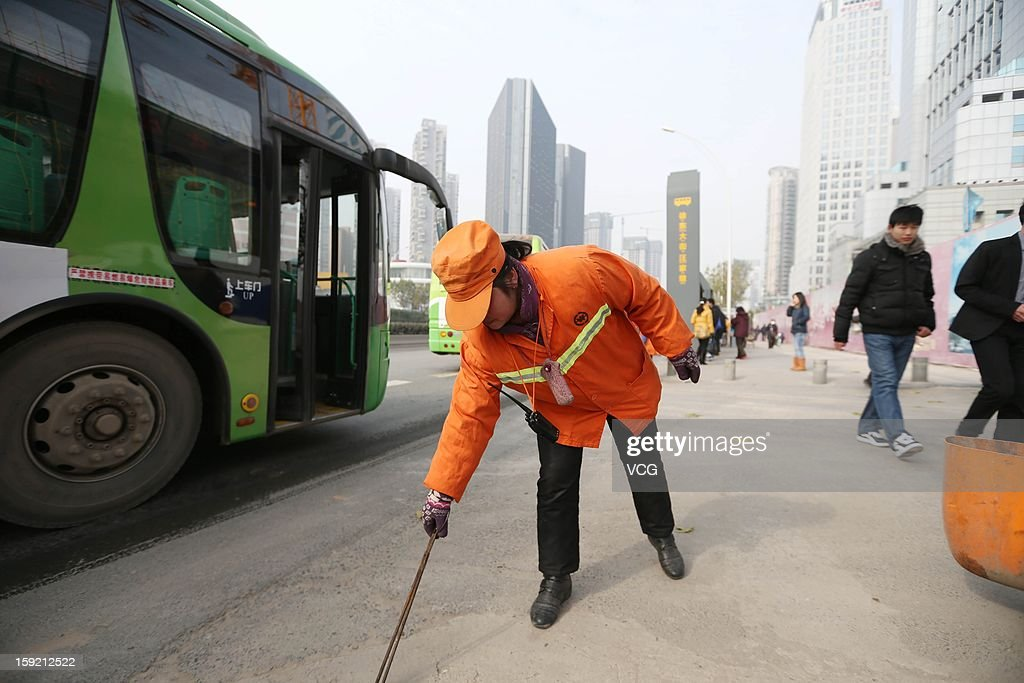 53-year-old Chinese real estate mogul Yu Youzhen works as a street cleaner on January 2, 2013 in Wuhan, Hubei Province of China. Yu Youzhen gladly wakes up at 3 a.m. six days a week earning about $228 a month to sweep almost two miles of roadway for one major reason: to set a good example for her children.