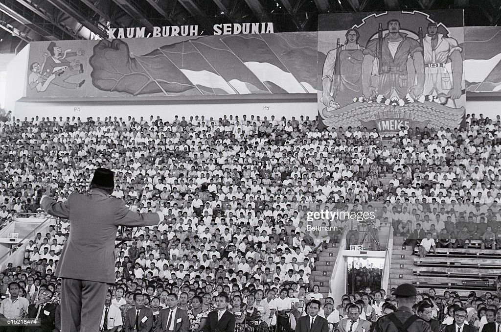 Djakarta, Indonesia- President <a gi-track='captionPersonalityLinkClicked' href=/galleries/search?phrase=Sukarno&family=editorial&specificpeople=209275 ng-click='$event.stopPropagation()'>Sukarno</a> of Indonesia addresses a mass May Day rally in the Sports Hall Building. <a gi-track='captionPersonalityLinkClicked' href=/galleries/search?phrase=Sukarno&family=editorial&specificpeople=209275 ng-click='$event.stopPropagation()'>Sukarno</a> announced his decision not to attend a peace conference with Malaysian Prime Minister Rahman in Tokyo. The announcement was viewed as a victory for Indonesia's powerful Communist Party. Posters above the silent crowd stress the unity of the working classes in their struggle to overcome 'imperialism.'