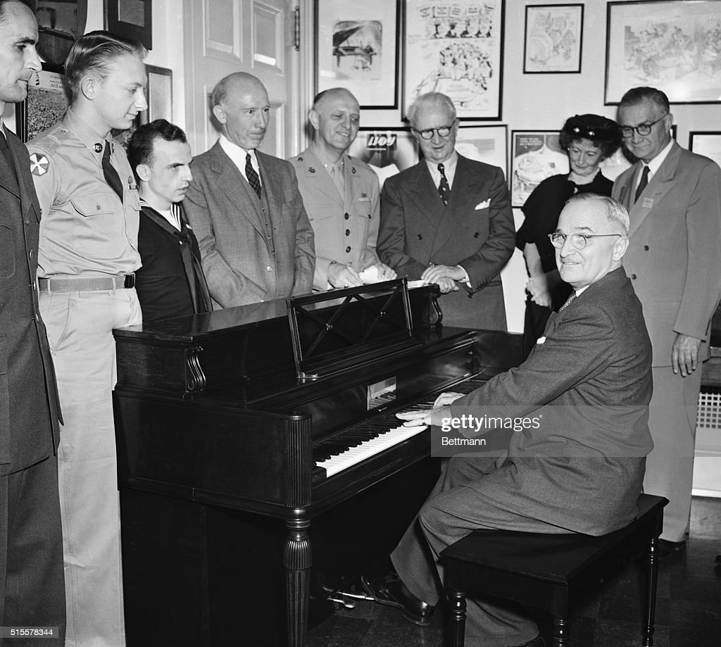 President Truman plays a few selections on his 'United Nations' spinet piano presented to him by today by the National Recreation Assn., as part of national Music Week. The piano is specially designed composite from materials contributed by varius UN Countries. looking on are: Johnny Green; Paul Carrino; Thomas Rivers; F. H. Santelman; Otto Harbach; Mrs. Robert Wood Bliss, and Justin Miller.