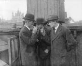 A group of men in hats and jackets congregate outside for a quiet smoke and to discuss the state of the economy