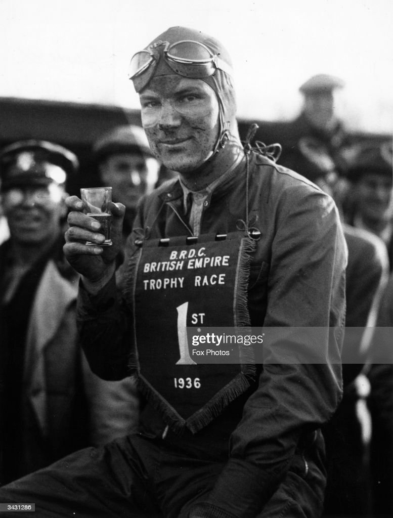 Dick Seaman winner of the British Empire Trophy Race at Donington Park celebrates with a drink