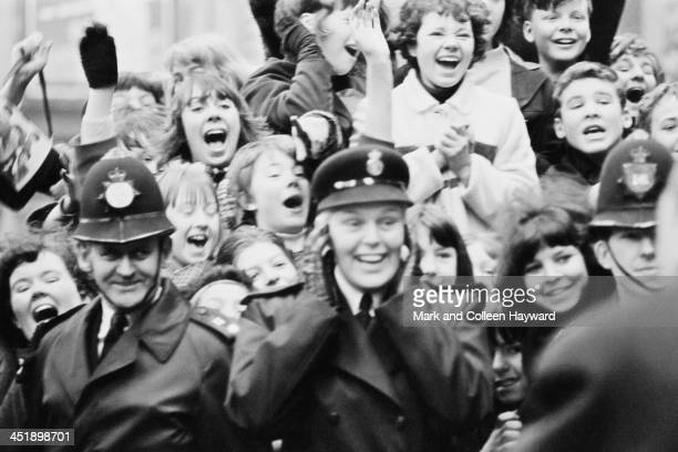 Police and fans of The Beatles line up at Marylebone Station in London to catch a glimpse of the band during the filming of 'A Hard Day's Night' on...