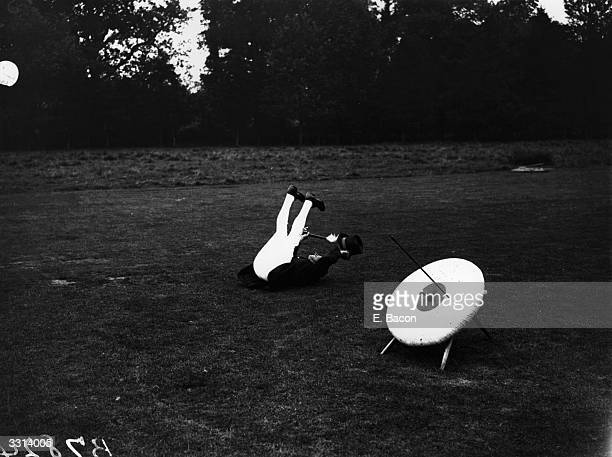 A 'marker' at an archery competition lying on his back and waving his legs in the air to record a bull's eye
