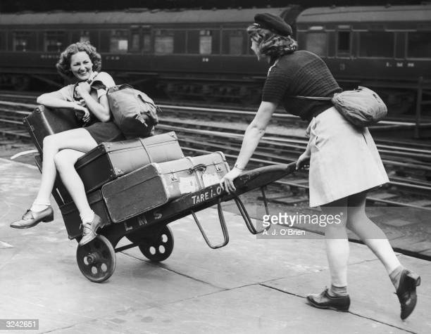 Two holidaymakers amuse themselves with a porter's trolley whilst waiting for their train at Euston Station London