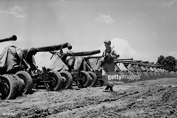 An American soldier guarding Bofors antiaircraft guns at a US Army supply depot in Manila in the Philippines