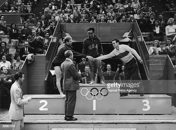 Olympic medal ceremony at the Empire Pool Wembley Men's Platform Diving Bruce Harlan second congratulates Joaquin Capilla Perez third and Samuel Lee...