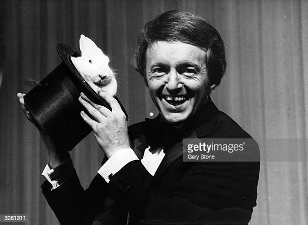 British magician and entertainer Paul Daniels with a white rabbit in a hat