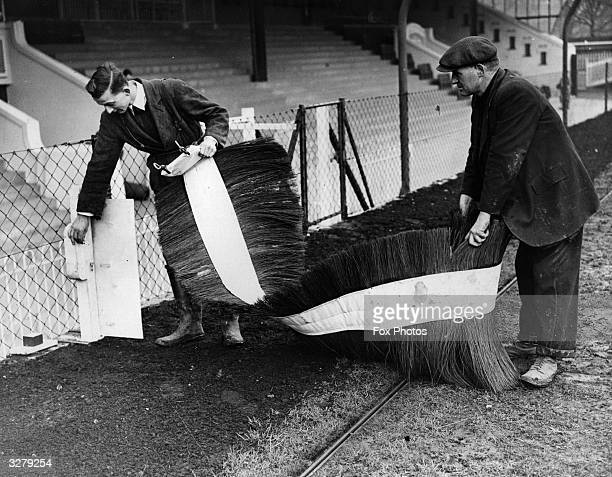 Workmen install a new more flexible type of hurdle at the Catford Stadium Greyhound track which will reduce the risk of injury to the dogs