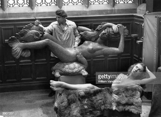 Model Joyce Taylor poses as sculptor Arthur Fleischmann works on the fins of a mermaid The sculpture is part of the showpiece Lockheed Fountain for...