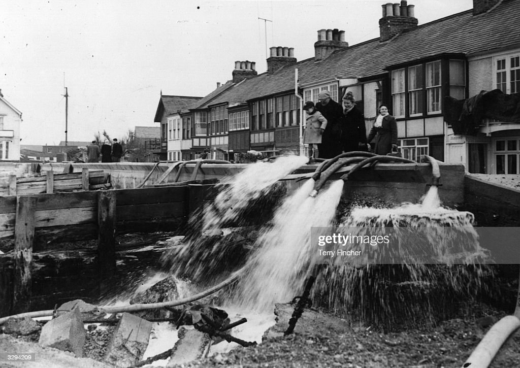 A group of people gather around hosepipes gushing out water from flooded homes and streets in Whitstable.