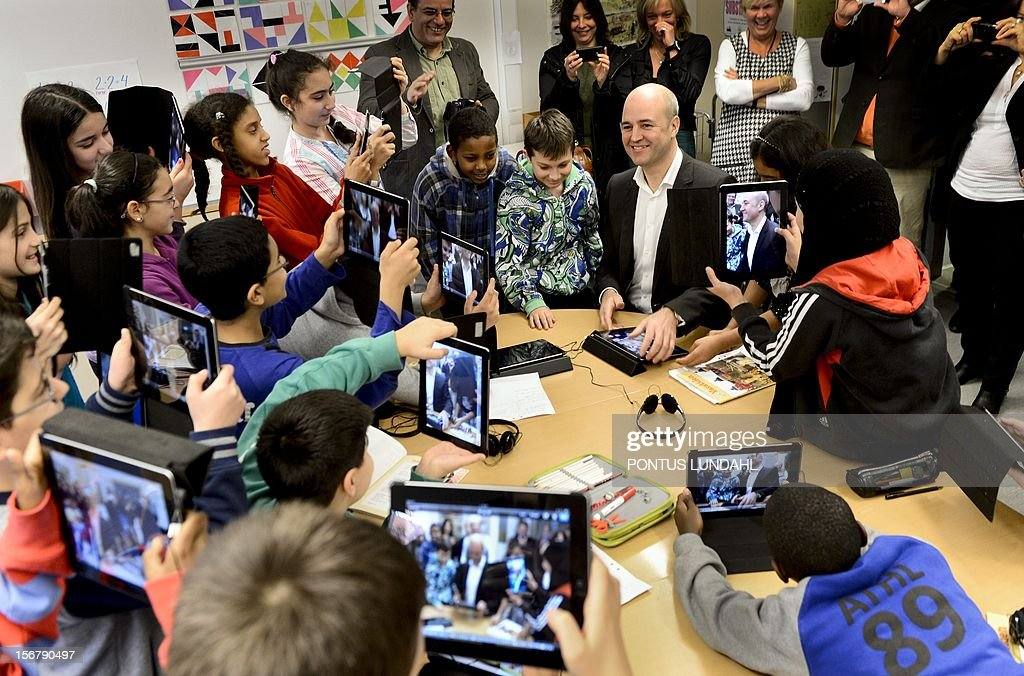5th graders use their iPads to take photos of Swedish Prime Minister Fredrik Reinfeldt (C) when he visits the Husby School west of Stockholm, Sweden, on November 21, 2012. Reinfeldt visited the school to learn more about the use of tablets in the education. AFP PHOTO / SCANPIX SWEDEN / Pontus Lundahl / ** SWEDEN
