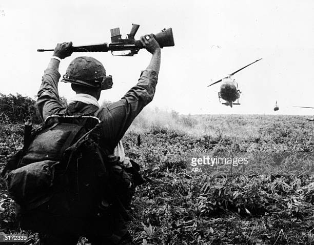 A soldier in the US Army 1st Air Cavalry holds his rifle above his head as he serves as a 'traffic cop' for helicopters landing in a field during an...