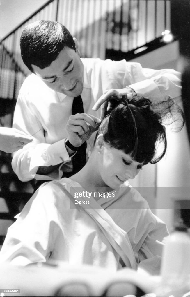 British hairdresser Vidal Sassoon cuts the hair of showgirl Beth Rogan. Sassoon pioneered geometric haircuts in Britain during the 1960's, and subsequently moved to California.