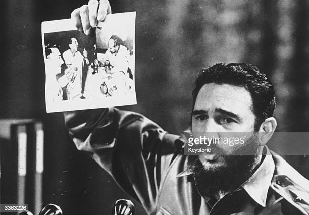 Cuban Prime Minister Fidel Castro presents a photograph in which General Ovando Candia and other men of the Bolivian Army get drunk to celebrate the...