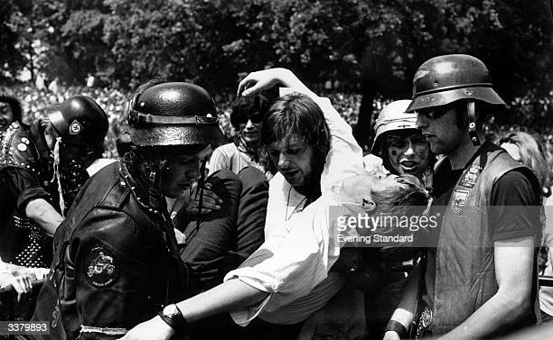 Hell's Angels acting as security at the free Rolling Stones concert in Hyde Park London lifting a fan to safety after he passed out