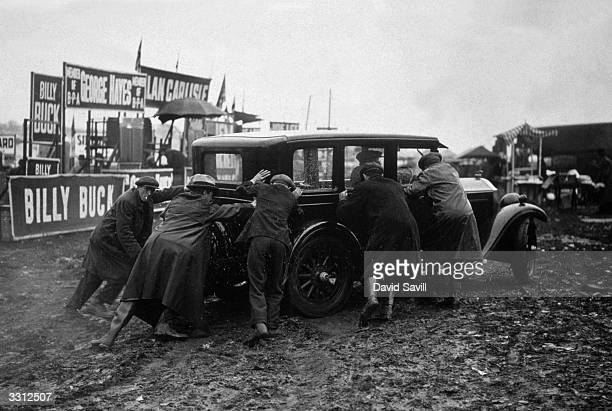 A group of men attempting to push a car out of the mud which had become stuck on The Hill at the Epsom Derby