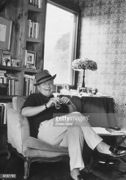 American author Truman Capote sits near a bookshelf with his legs crossed in his home in Sagaponack Long Island New York