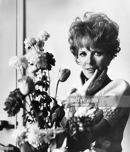 Pop singer Petula Clark posing next to a bunch of flowers