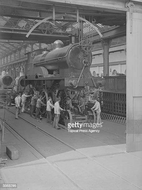 The Coronation engine at the London and North Western Railway Works in Crewe The workmen are fitting the body of the steam engine to the bogie