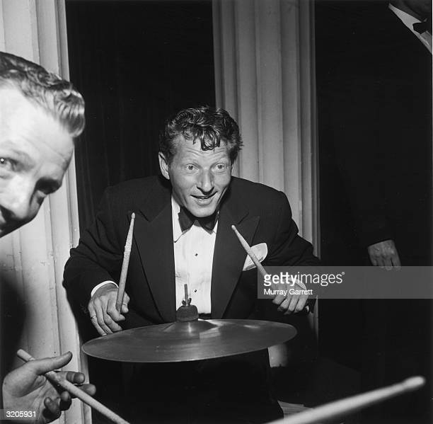 EXCLUSIVE American actor Danny Kaye sits behind a cymbal holding two drum sticks during Betty Hutton's party celebrating the wedding of Hollywood...