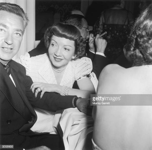 EXCLUSIVE Frenchborn actor Claudette Colbert sits with her husband Dr Joel Pressman while attending actor Betty Hutton's party to celebrate the...