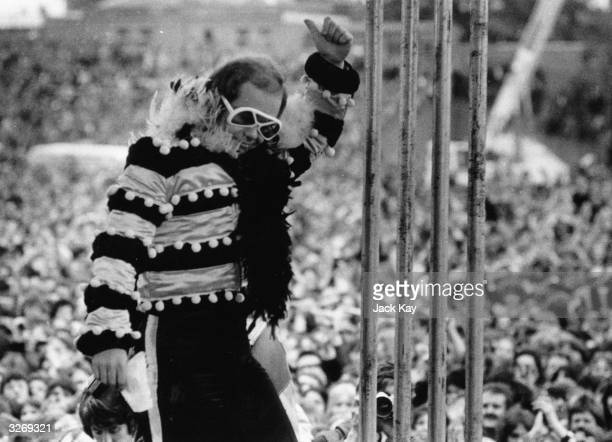 British pop singer and pianist Elton John on stage before a vast crowd at an openair concert