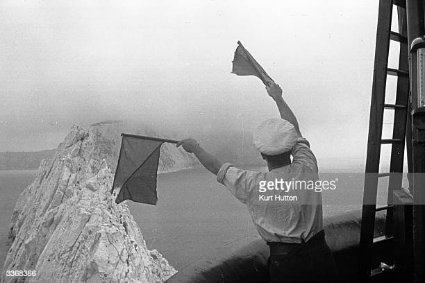 A lighthouse operator signalling to the shore with semaphore flags from the Needles lighthouse off the coast of the Isle of Wight Original...