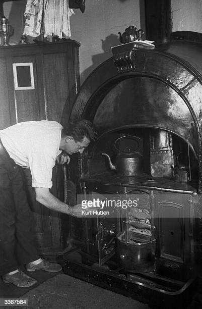 An operator of the Needles lighthouse off the coast of the Isle of Wight preparing a meal in the lighthouse's Aga stove Original Publication Picture...
