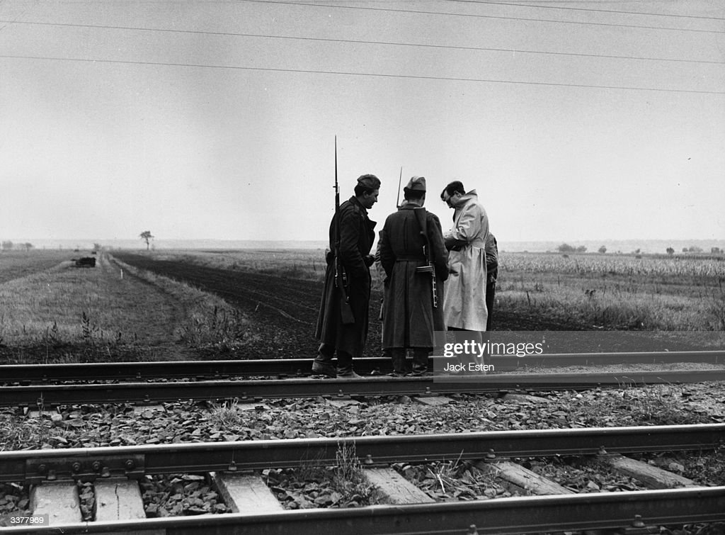 Trevor Philpott of Picture Post talks to Hungarian soldiers who are guarding the Austro-Hungarian frontier. The broad line of uncultivated land running into the distance beyond the railway line is the actual border. Original Publication: Picture Post - 8724 - Lace Curtain View Of A Revolt - pub.1956