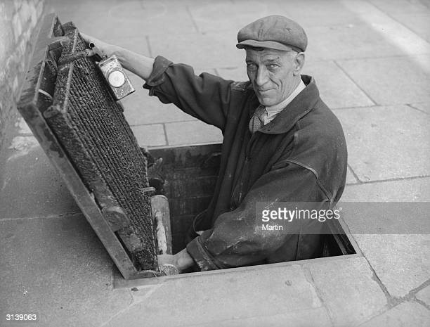 London sewerman Jack O'Brien climbing into a sewer He is to be interviewed on his work for the BBC radio programme 'In Town Tonight'