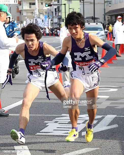 5th runner of Meiji University Hiroki Oe receives the sash from 4th runner Genki Yagisawa during day one of the 88th Hakone Ekiden on January 2 2012...