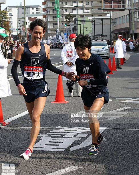 5th runner of Toyo University Ryuji Kashiwabara receives the sash from 4th runner Masaya Taguchi during day one of the 88th Hakone Ekiden on January...