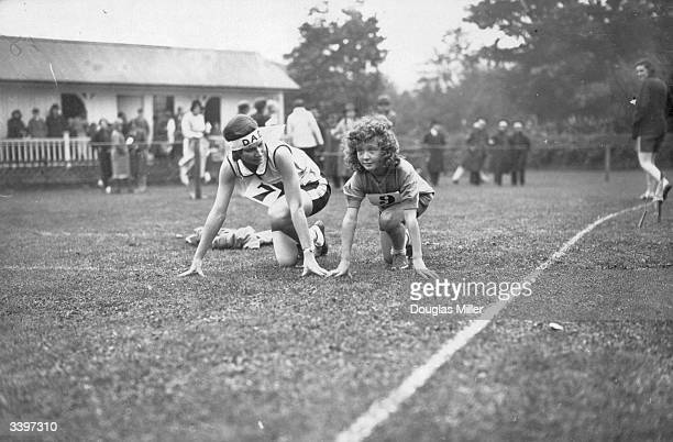 Miss Q Goodacre of Durban South Africa gives a few hints on starts to Doreen Tanner the youngest competitor at the annual sports gala of the Wycombe...