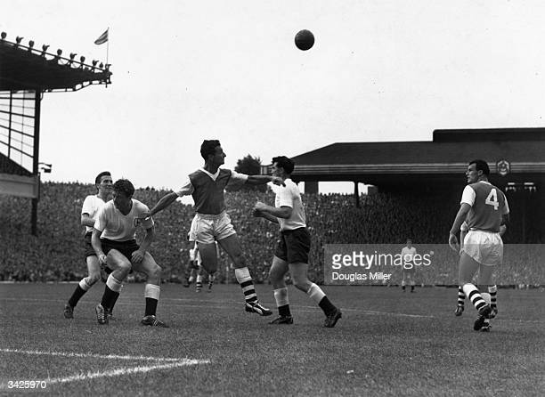 Arsenal right back Les Wills heads the ball clear from three attacking Tottenham Hotspur players as the two teams meet in a North London derby match...