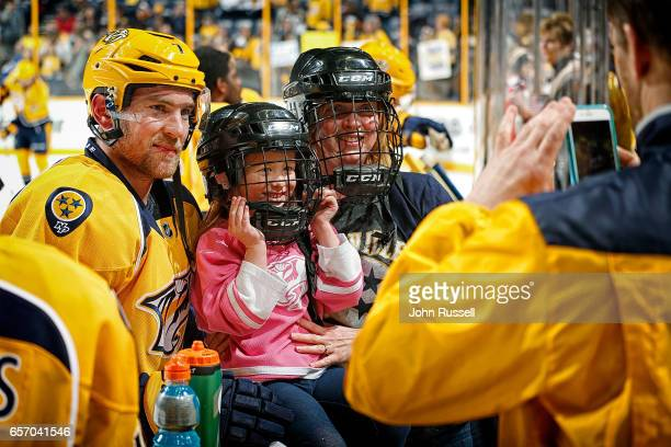 5yearold Emma Kate Clanney and her mother Jessica pose with Yannick Weber of the Nashville Predators during warmups prior to an NHL game against the...
