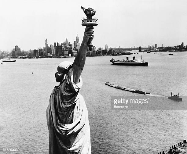 A striking view of New York Harbor and the magnificent skyline of lower Manhattan made from behind the Statue of Liberty who stands with torch aloft...