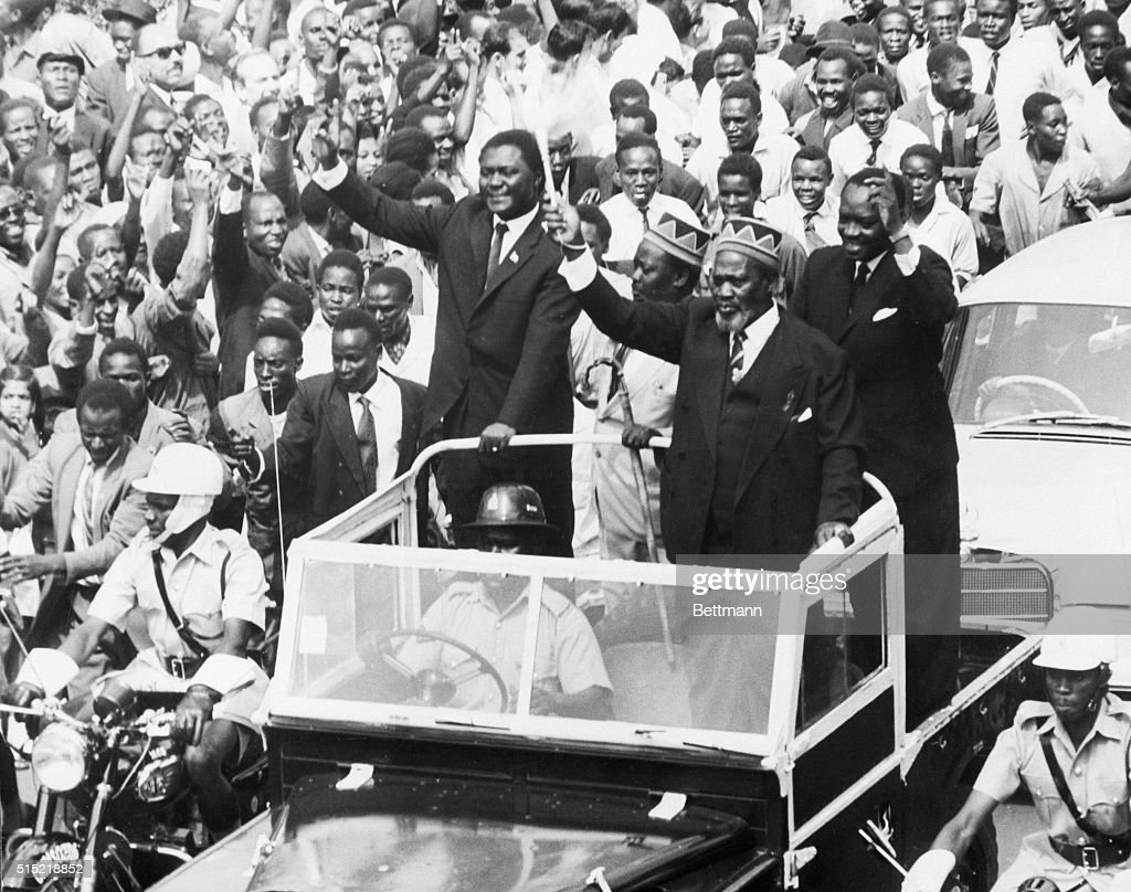 Nairobi, Kenya- Waving his 'wisk' the newly-elected Premier of Kenya, <a gi-track='captionPersonalityLinkClicked' href=/galleries/search?phrase=Jomo+Kenyatta&family=editorial&specificpeople=211508 ng-click='$event.stopPropagation()'>Jomo Kenyatta</a>, (R, foreground), greeted throngs of cheering citizens as he rode through the streets of Nairobi. Accompanying Kenyatta are Tom Mboya, (L), Minister of Justice and Constitutional Affairs; A. Oginga Odinga, Minister for Home Affairs; and James S. Gichuru, Minister for Finance. The motorcade was part of the National Holiday celebrations which marked the start of internal self-government for the African nation.