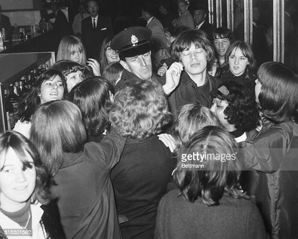 6/1/1964London England Mick Jagger singer with the 'Rolling Stones' gets assistance from the law at London Airport today when he was mobbed by...