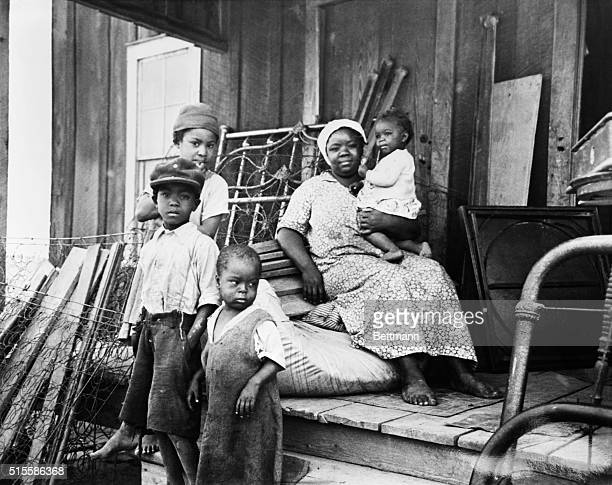 African American mother with baby and three small children seated on the front porch of a cabin with belongings piled around her A family to be moved...