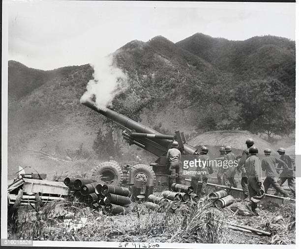 As smoke from the previous round curls about the hot barrel crewmen of this US eightinch Howitzer move quickly to ram another charge into the breech...